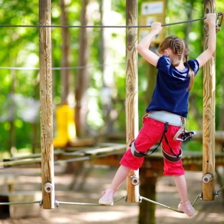 Adorable little girl enjoying her time in climbing adventure park